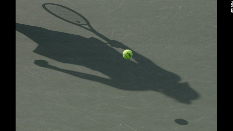 A shadow is cast across the court as Denmark's Caroline Wozniacki  serves against  Arantxa Rus of the Netherlands, during the first day of the Korea Open at Olympic Park Tennis Stadium on Tuesday in Seoul, South Korea.
