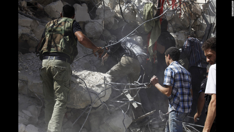 People pull out bodies from under the rubble of a destroyed building in Aleppo on Wednesday.