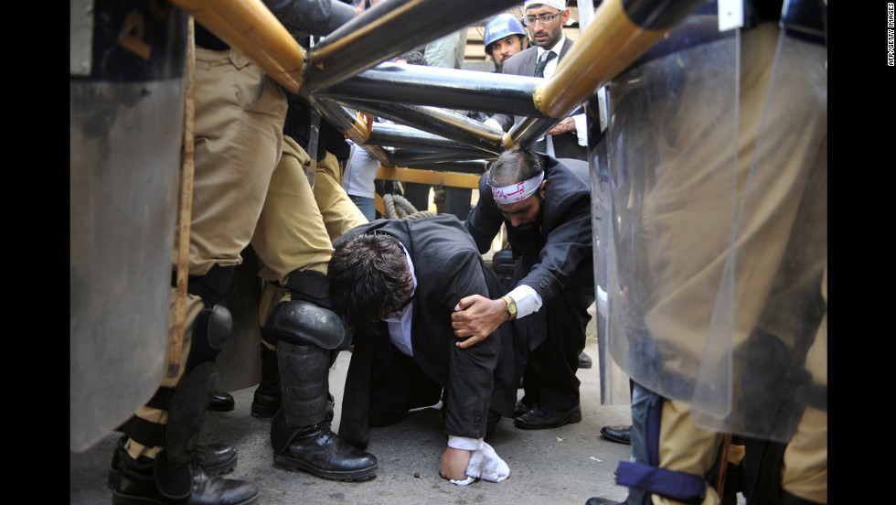 Police try to stop Pakistani lawyers crawling under a barrier as they try to reach the U.S. Embassy in the diplomatic enclave during a protest against an anti-Islam movie in Islamabad on Wednesday. Up to 500 Pakistani lawyers managed to enter the heavily guarded enclave as a fresh wave of protests  erupted across Pakistan.