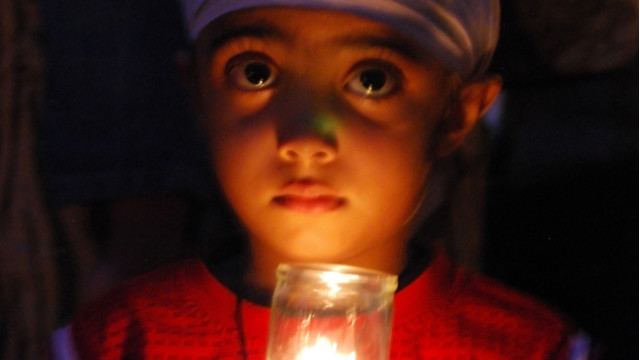 Akandeep Delam, 4, holds a candle in honor of six people killed in an attack at the Sikh temple in Oak Creek, Wisconsin.