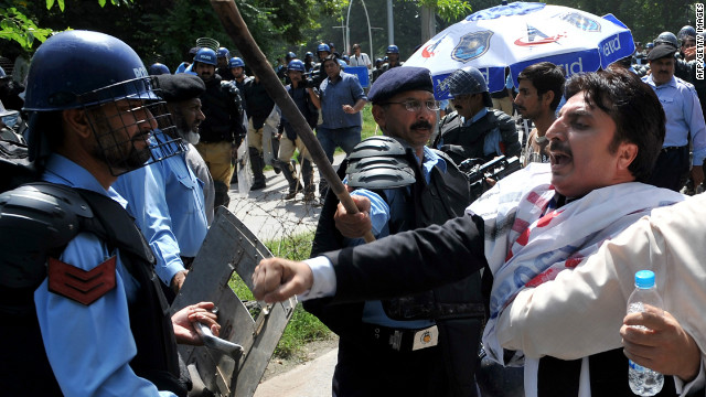 "Pakistani riot policemen hold back lawyers shouting anti-US slogans as they attempt to reach the US embassy in the diplomatic enclave during a protest against an anti-Islam movie in Islamabad on September 19, 2012. Up to 500 Pakistani lawyers on  managed to enter the heavily guarded diplomatic enclave in a fresh wave of protests that erupted across Pakistan to denounce an anti-Islam film. More than 30 people worldwide have died in incidents linked to the trailer for ""Innocence of Muslims,"" a US-made film that depicts the Prophet Mohammed as a thuggish womaniser.  AFP PHOTO / AAMIR QURESHI        (Photo credit should read AAMIR QURESHI/AFP/GettyImages)"