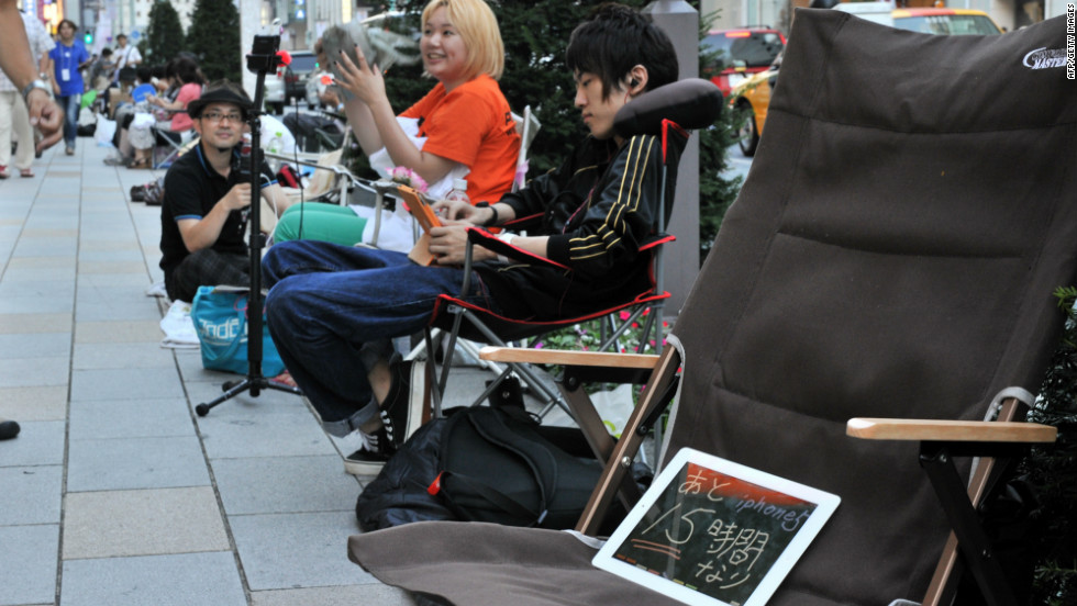"Apple fans line up outside an Apple Store in Tokyo on Thursday. The iPad in the chair reads ""15 hours more for iPhone 5."""