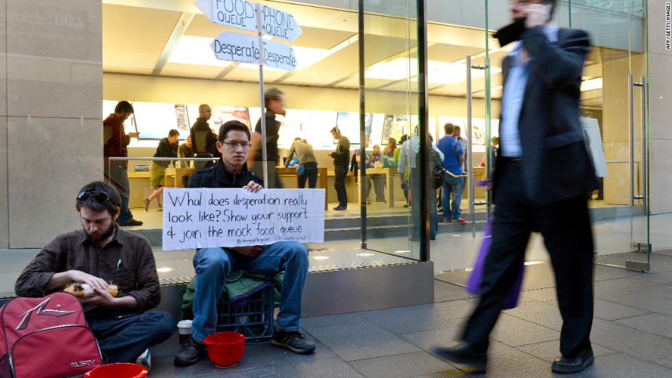 Francis Le holds up a placard in his mock food queue outside Apple's flagship store in Sydney on Thursday in a form of protest against people waiting to buy the iPhone 5. Le is seeking to highlight what he calls the madness of endless consumption and to contrast it with desperate, hungry people around the world.