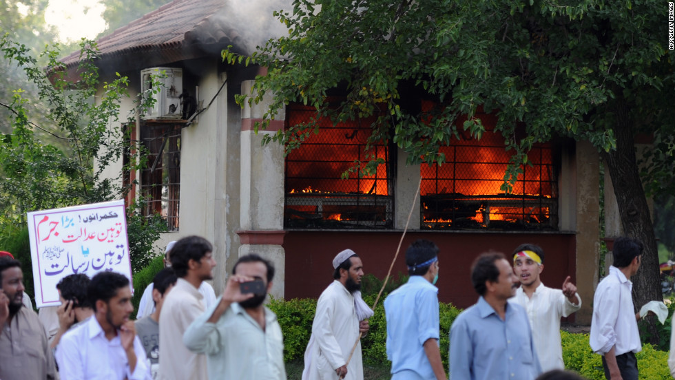 Pakistani protesters walk near a burning police bunker as demonstrators attempt to reach the U.S. Embassy in Islamabad on Thursday, September 20.