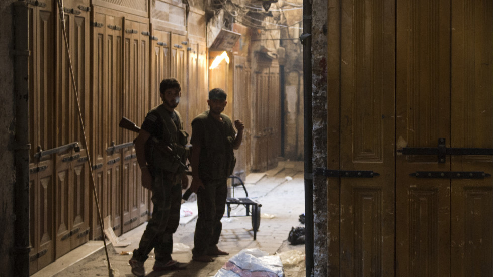 Syrian rebel fighters in position at a deserted market in Aleppo on Thursday.