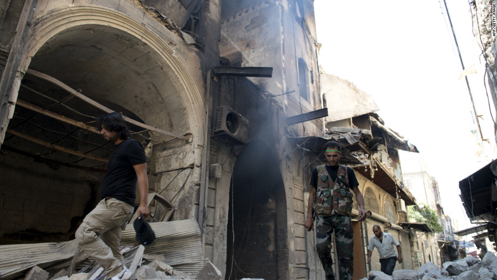 Fighters and civilians walk past buildings damaged during fighting between rebel and government forces in Aleppo on Thursday.