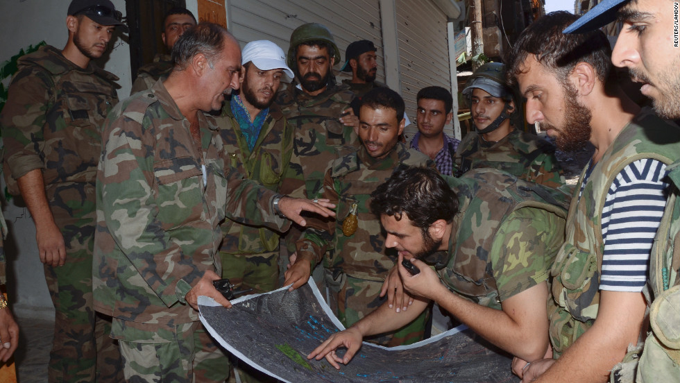 Syrian troops look at a map of the Suleiman al-Halabi neighborhood in Aleppo on Thursday.