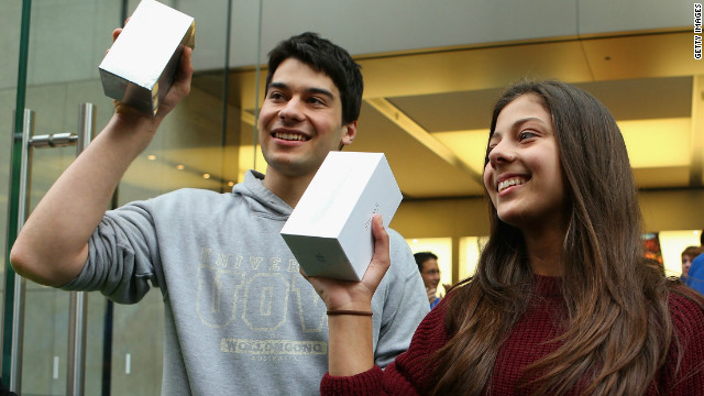 The first customers to purchase their new iPhone 5s exit an Apple store in Sydney, Australia.