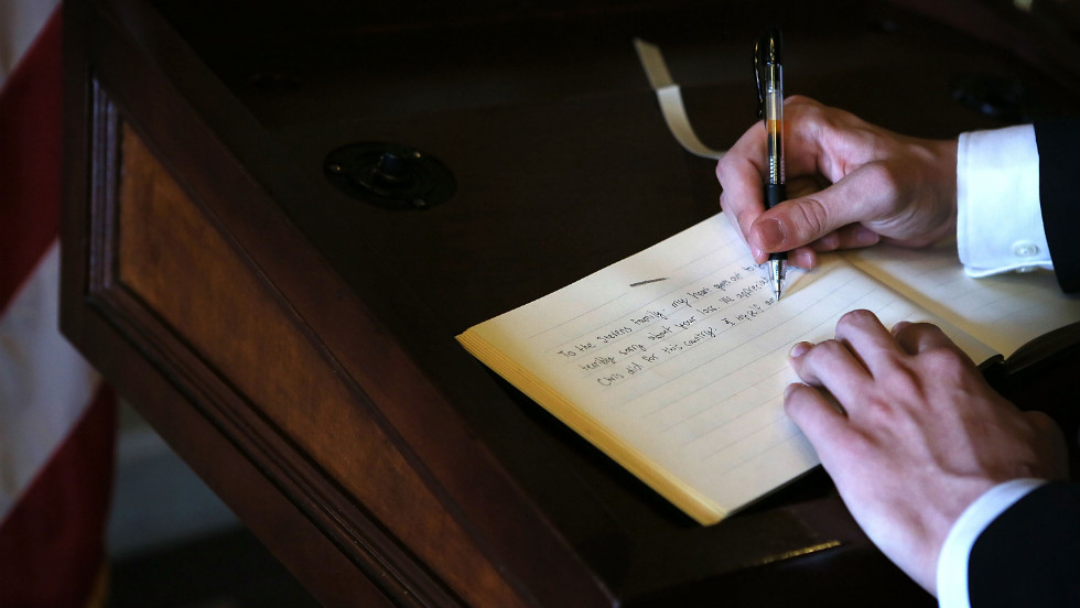Intern Chris Jobson of the Senate Democratic Media Center signs the condolence book for Ambassador J. Christopher Stevens at the U.S. Capitol on Friday in Washington.