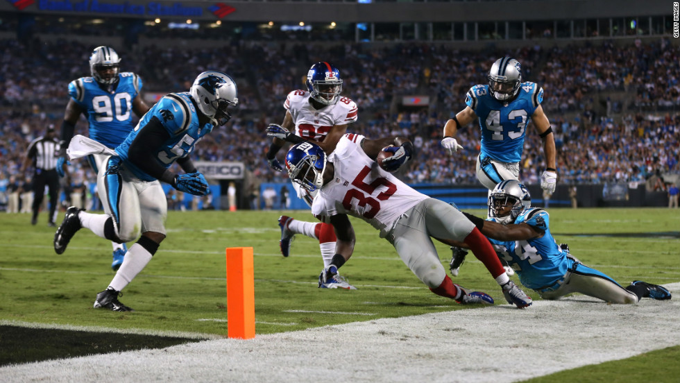 Andre Brown of the Giants runs the ball down to the 2-yard line in the second quarter on Thursday against  Josh Norman of the Carolina Panthers.