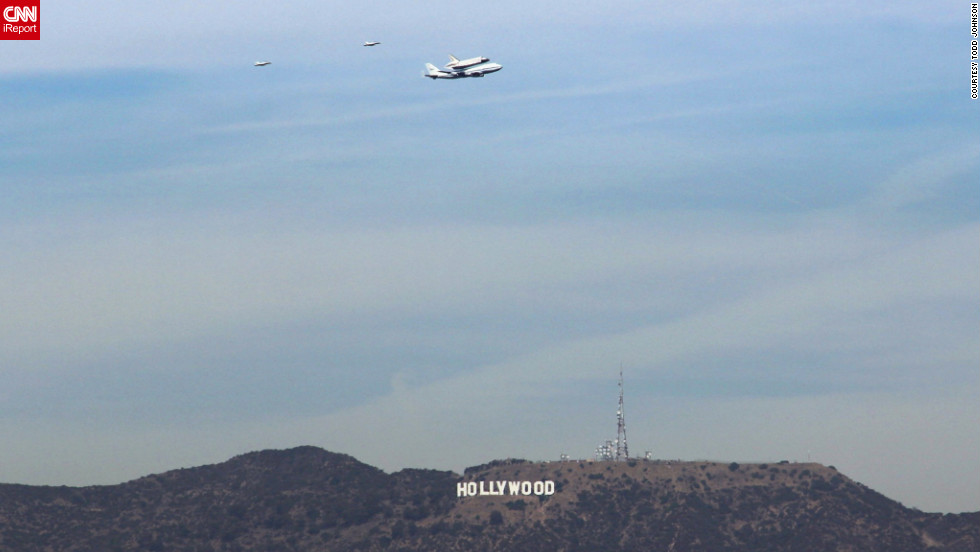 "Endeavour flies low <a href=""http://ireport.cnn.com/docs/DOC-844966"">over the Hollywood sign</a> as it travels toward its final destination in Los Angeles on Friday."