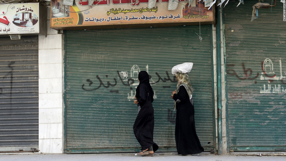 Syrian women walk past closed shops in Aleppo on Friday.