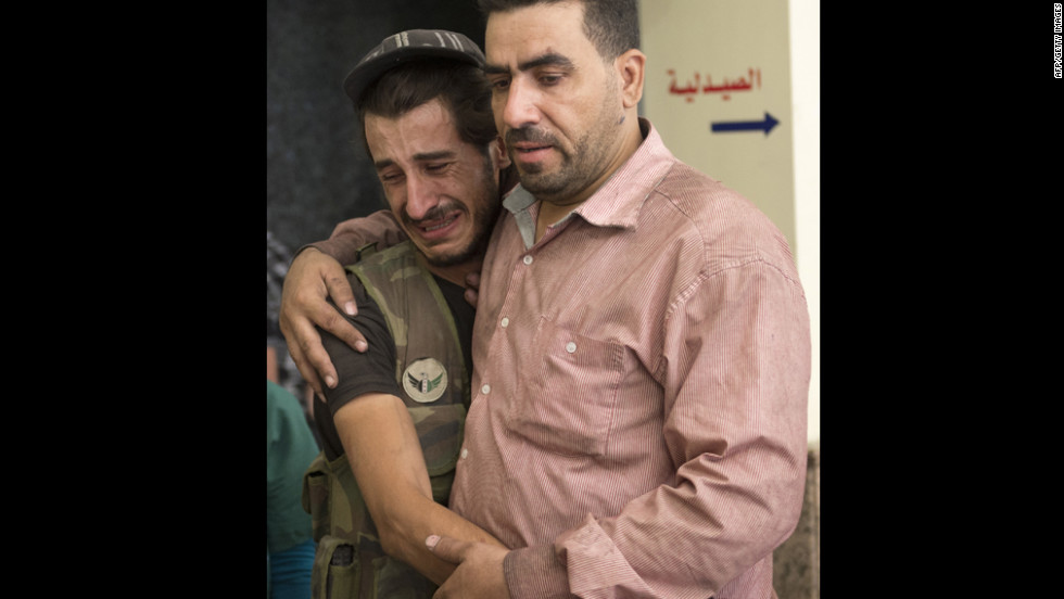 A Syrian rebel is comforted by a friend as he mourns the death of a comrade at a hospital in Aleppo on Friday.
