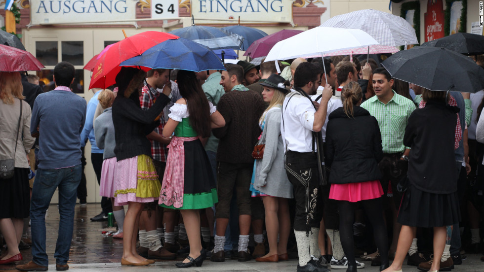 Visitors hold umbrellas as they wait in front of a beer tent.