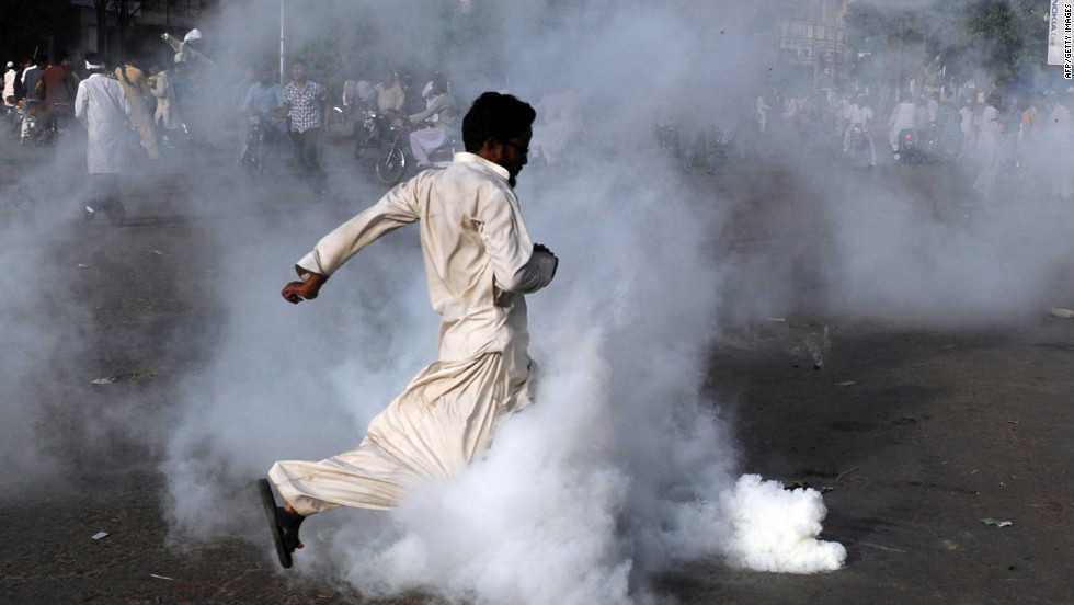 A demonstrator kicks a tear gas shell in Karachi, Pakistan, on Friday.
