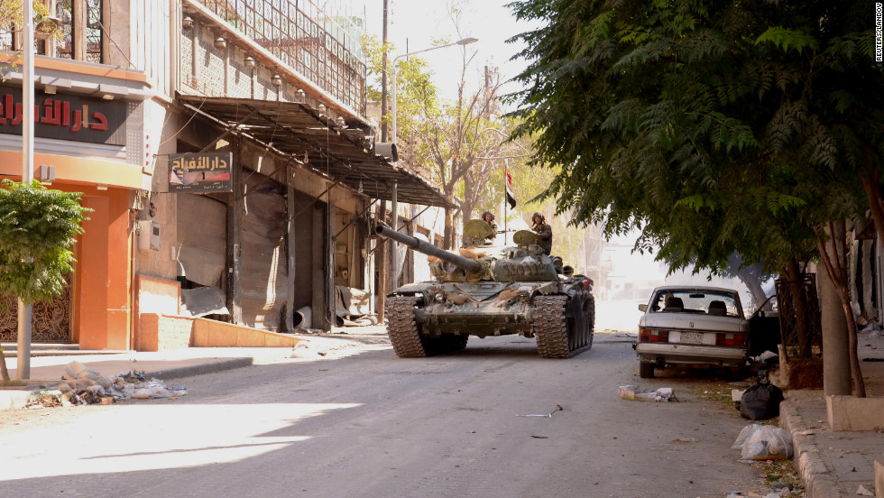 Soldiers loyal to President Bashar al-Assad travel in a Syrian Army tank in Aleppo  on Sunday, September 23, after clashes between Free Syrian Army fighters and regime forces.