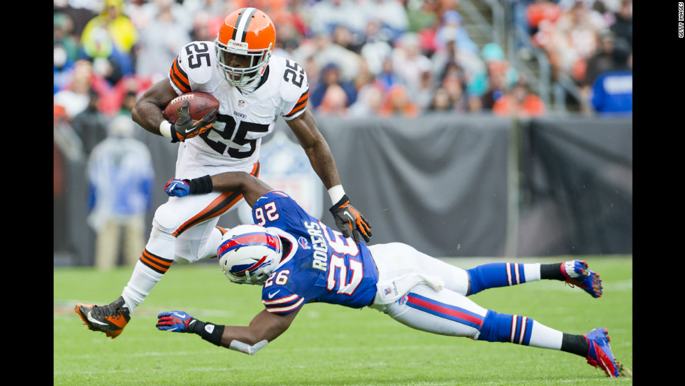 Chris Ogbonnaya of the Browns jumps over Justin Rogers of the Bills on Sunday.