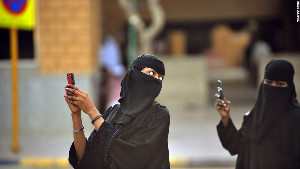 Saudi women take pictures with their mobile phones after the end of a prayer performed on the first day of Eid al-Fitr in August 2012 to mark the end of the holy fasting month of Ramadan. Close behind the United States, 9.6% of all mobile devices in Saudi Arabia have been infected by malware.