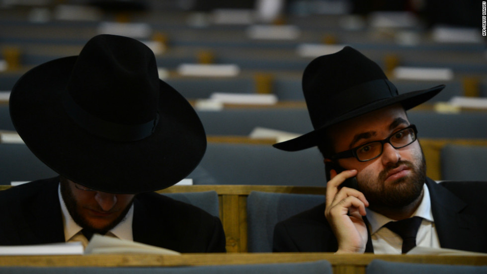 A man uses his phone before a ceremony to ordain four rabbis in a German synagogue.