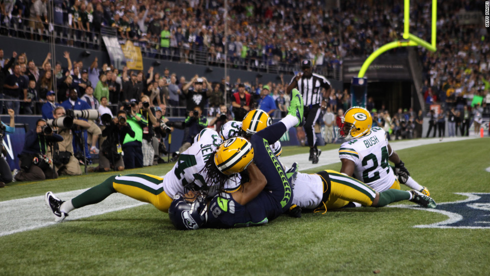 The group falls to the ground in the end zone. Packers defensive back M.D. Jennings appeared to intercept the pass and had both hands wrapped around the ball with the ball pulled into his chest.