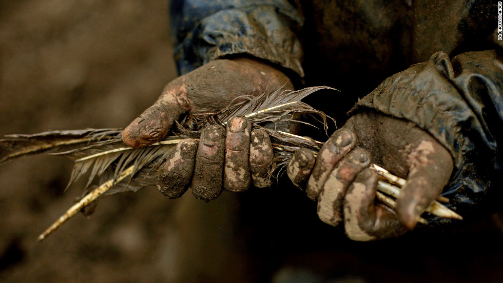 Ger Lyons, a competitor at the National Ploughing Championships, holds feathers used to mark out the furrows in the mucky conditions Tuesday in New Ross, Ireland.