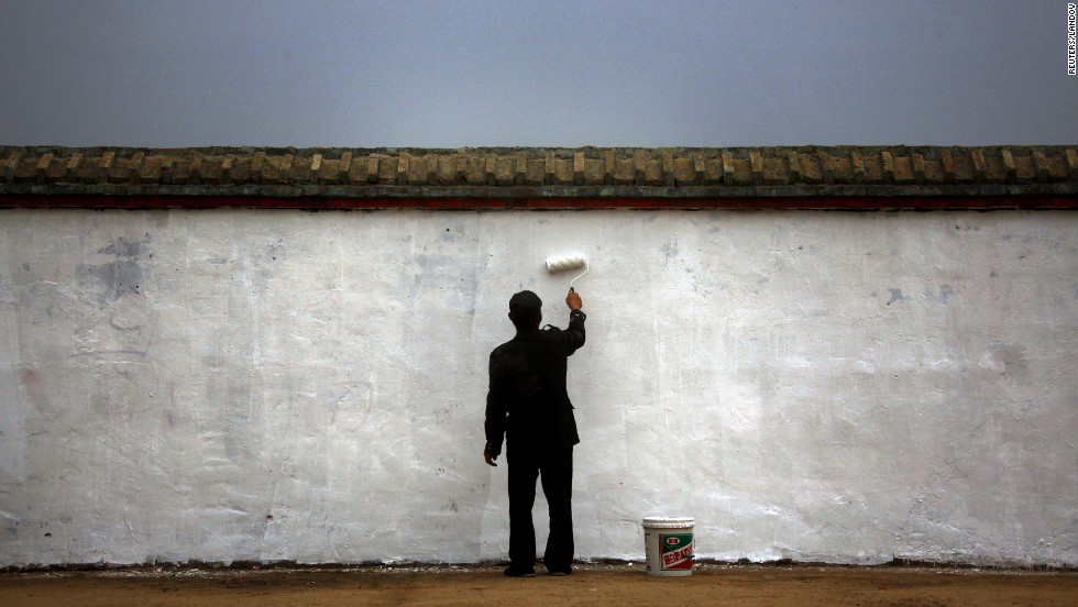 A man paints a wall surrounding a village on the outskirts of Beijing on Tuesday.
