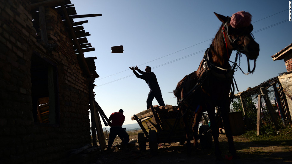 Roma men salvage material from a home before it gets bulldozed Tuesday in a Roma settlement in Maglizh, Bulgaria. More than 30 illegally built Roma houses were demolished.