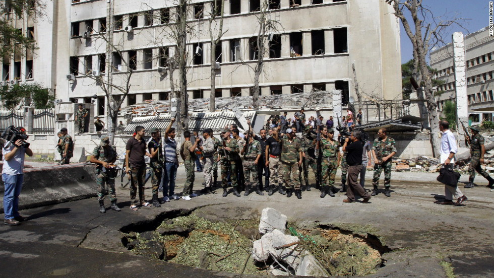 "Syrian soldiers stand at the site of bombings Wednesday near the headquarters of the armed forces general staff in Damascus. The government said a fight was under way to ""cleanse"" rebels from the targeted building -- the office of the joint chiefs of staff -- but military officials are fine."