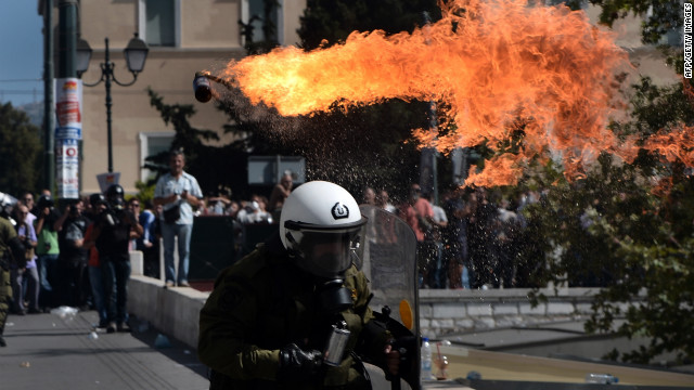 Firebombs explode in front of riot police on September 26, 2012 in Athens during clashes with demonstrators at a 24-hours general strike. Police in Athens clashed with hooded youths throwing firebombs on the sidelines of a large demonstration against a new round of austerity cuts.    AFP PHOTO / ARIS MESSINIS        (Photo credit should read ARIS MESSINIS/AFP/GettyImages)