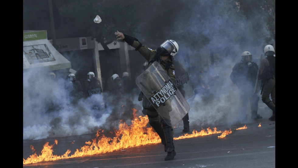 A police officer throws a stone toward demonstrators Wednesday.