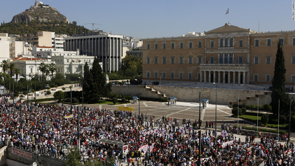 Demonstrators march by the parliament during the strike on Wednesday.