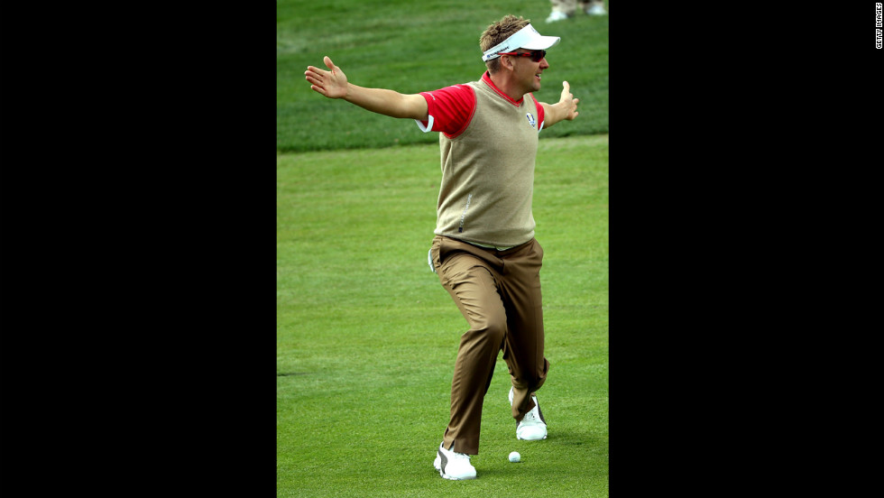 Ian Poulter of Europe stands over a ball in the fairway Thursday.