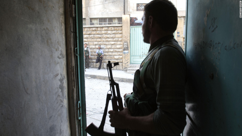 A rebel fighter looks out a doorway during fighting in Aleppo on Thursday.