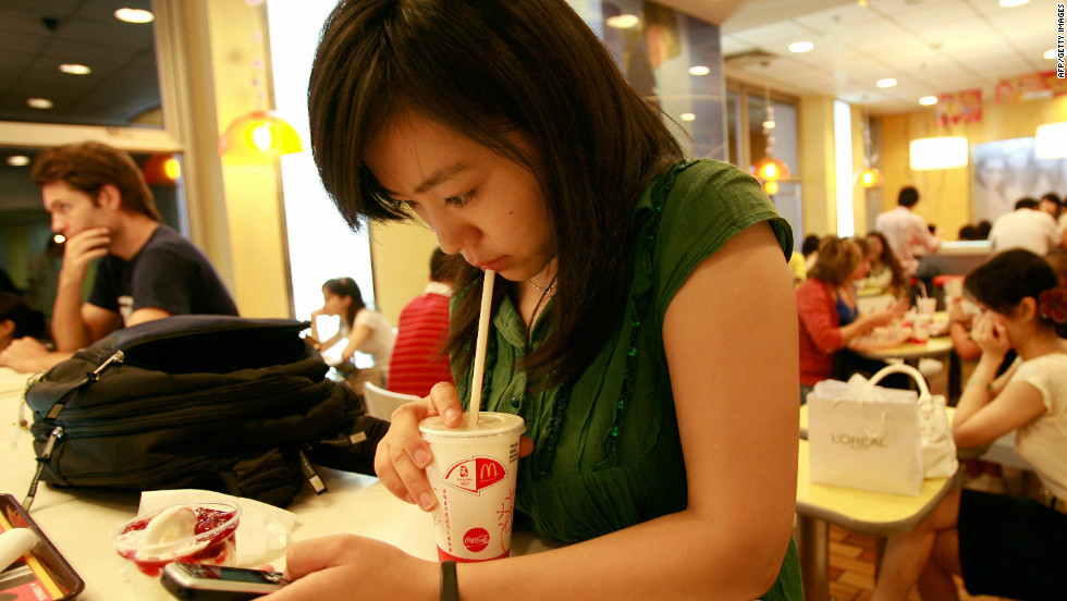 A young woman uses her mobile phone at a fastfood outlet in Beijing, China. More than 1 in 4 mobile devices are infected with malware in the world's most populous country, according to NQ Mobile. <br />