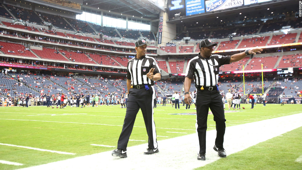 NFL officials wave to the fans during the pre-game warmup on Sunday at the Tennessee Titans-Houston Texans game.