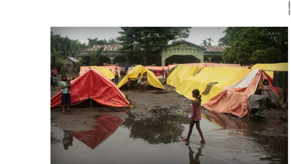 Prolonged monsoon rains in Assam flood the courtyards of schools being used as relief camps, forcing those who have taken refuge in tents to sleep many nights on the buildings' verandas and in hallways.