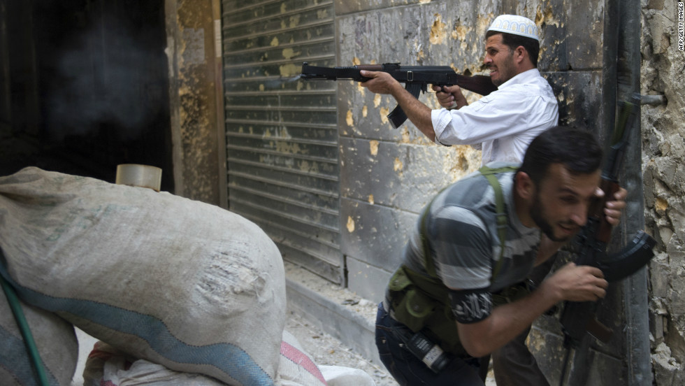 "A Syrian rebel fires toward regime forces as his comrade ducks for cover during clashes in Aleppo in northern Syria on Sunday, September 30. Click through the gallery to view images of the fighting in September. <a href=""http://www.cnn.com/2012/10/09/world/gallery/syria-unrest-august/index.html"" target=""_blank"">See photographs of the fighting in August.</a>"