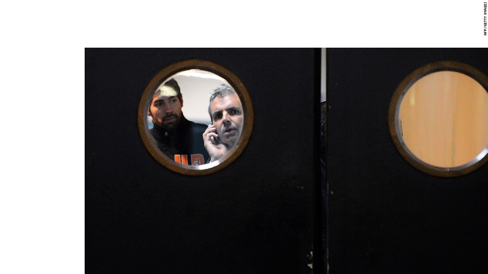 Nikola Karabatic, left, a member of a Montpellier handball team rocked by allegations of match-fixing, prepares to leave an arena in Paris on Sunday under police escort.