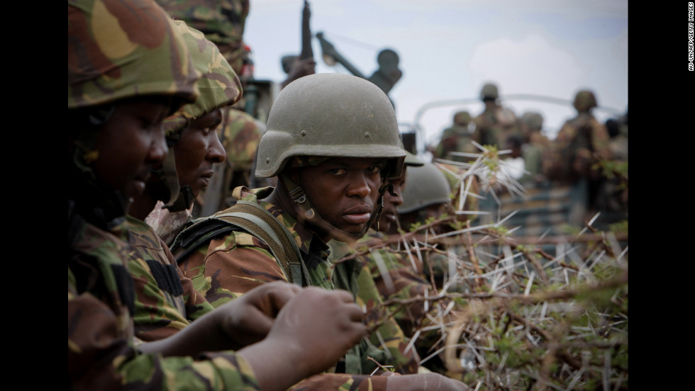 Kenyan troops sit on a flatbed truck Tuesday as a convoy of African Union and U.N. troops makes its way from the sea port to the airport in Kismayo, Somalia.