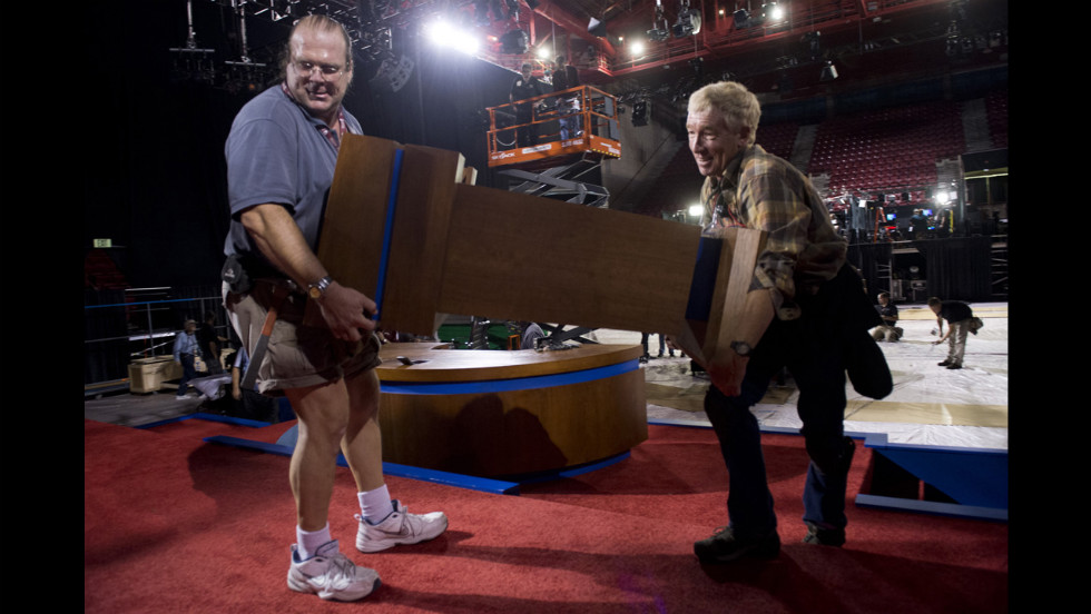 Workers carry a podium onto the stage on Monday.