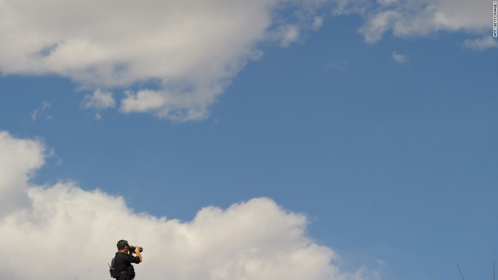 A member of the U.S. Secret Service keeps watch from the top of a building as Obama takes part in a debate walk-through at the University of Denver on Wednesday.
