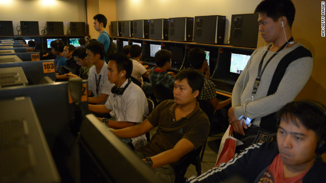 Customers at an Internet cafe look at Facebook profiles that have turned black in protest against a new cybercrime bill.