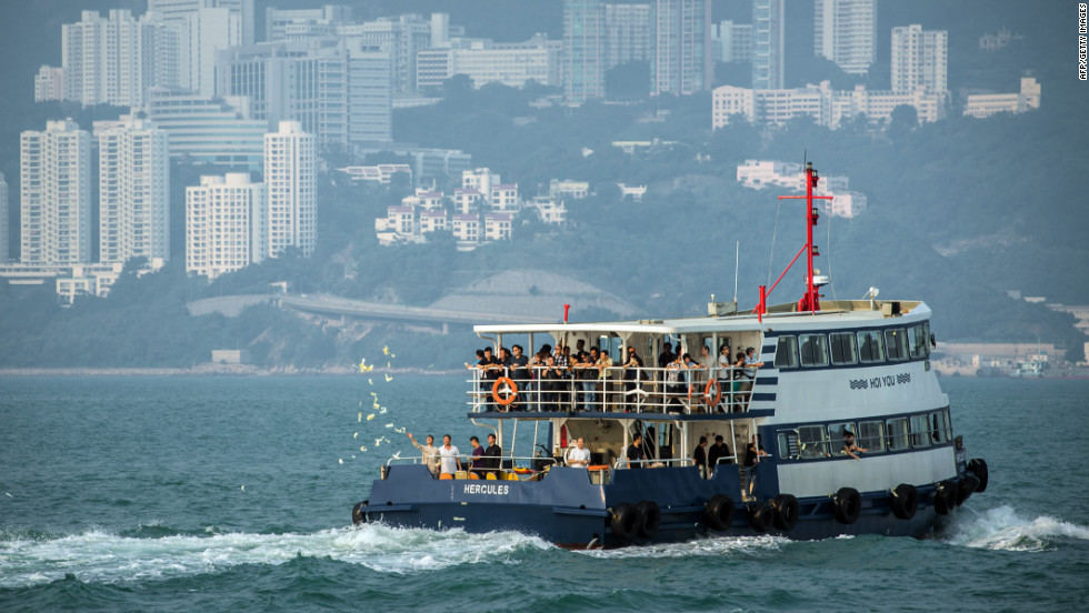 Mourners accompanied by Taoist priests take boats on Thursday, October 4, to go to the scene of the boat collision that killed 38 people off Lamma Island, near Hong Kong, on October 1. They throw paper offerings for the dead into the sea.