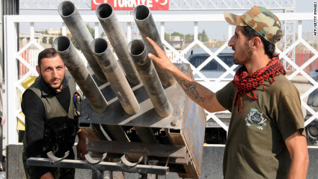 Syrian rebel fighters look at a multi-rocket launcher in Tal Abyadh, a Syrian town close to the Turkish border, on Thursday.
