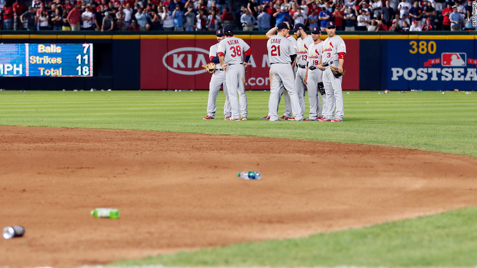Cardinals players stand on the field as debris is removed.