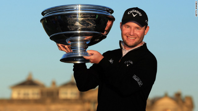 Branden Grace holds the winning trophy aloft after claiming victory in the Dunhill Links Championship.