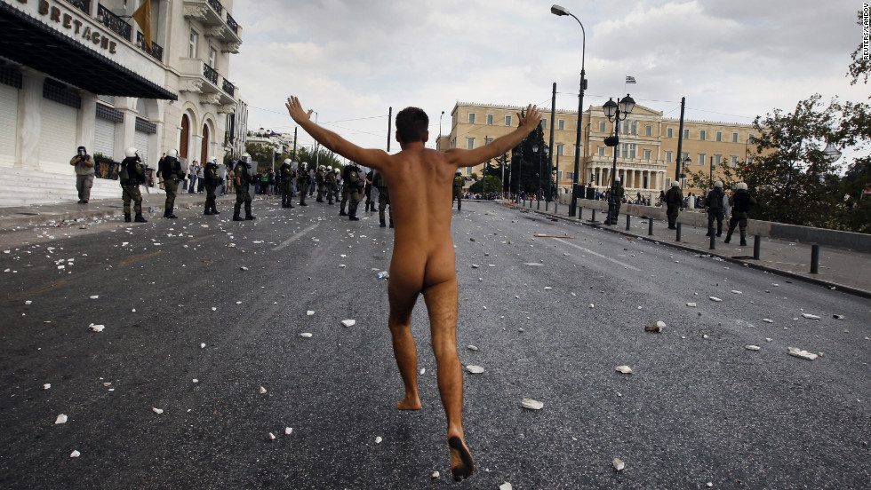 A naked protester runs past the parliament in Syntagma Square.