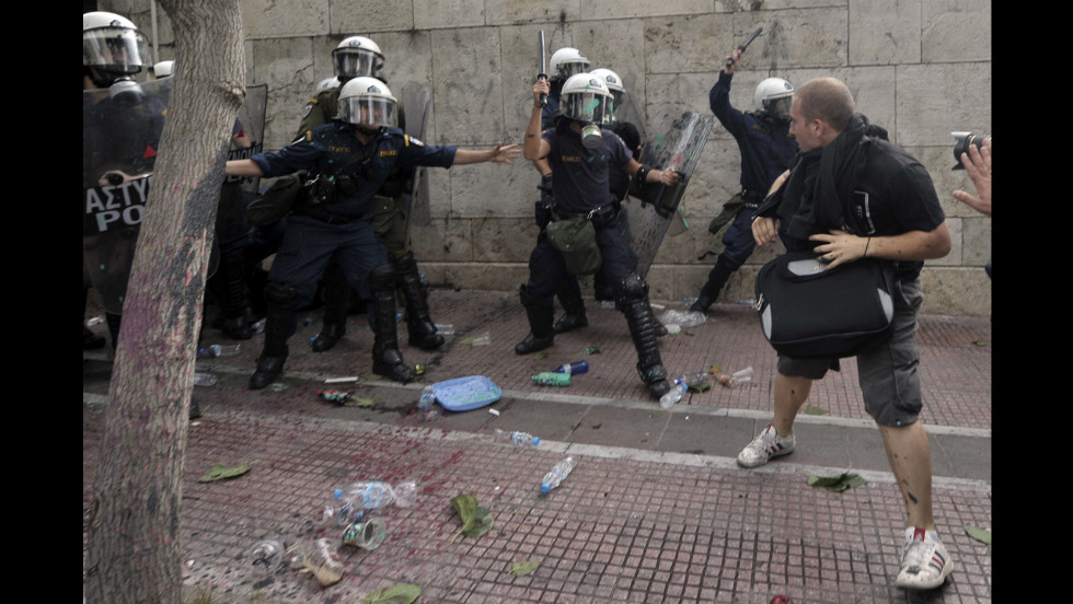 Demonstrators clash with riot police protecting the Greek parliament.