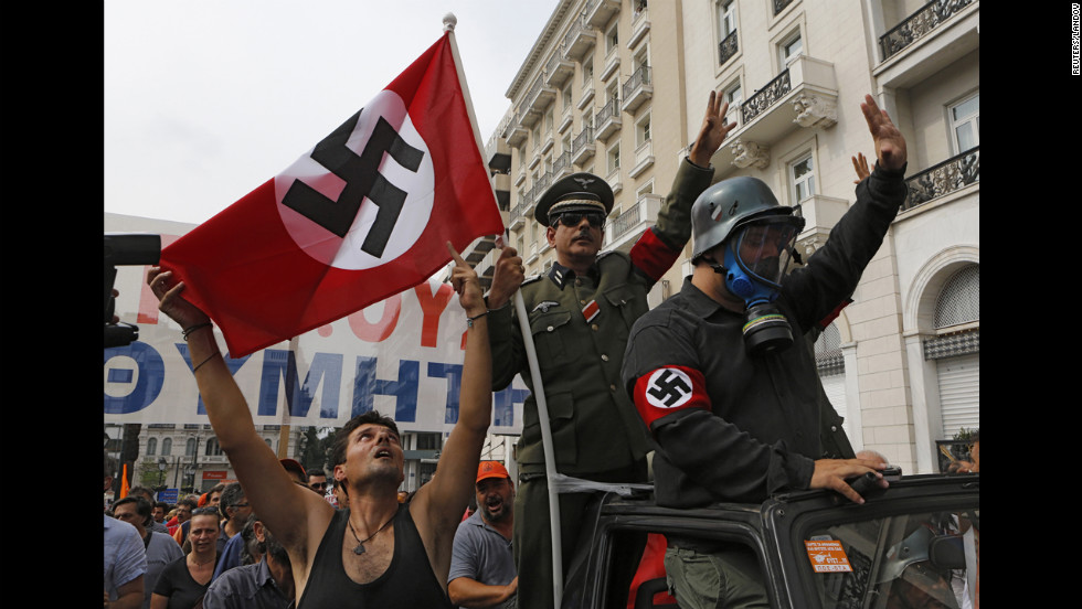 Demonstrators dressed as Nazis ride in an open-top car in Syntagma Square.
