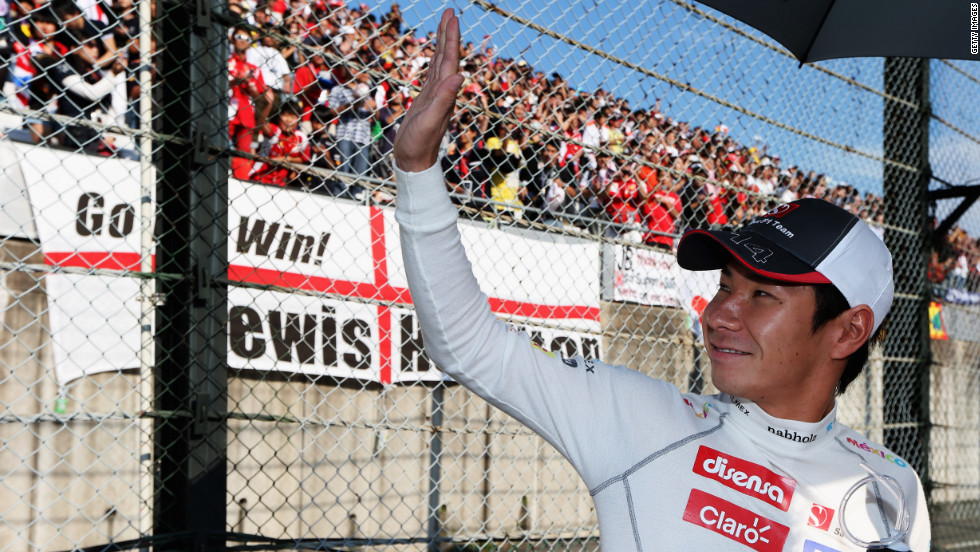 Kobayashi waves to an adoring crowd as he prepares to drive in his maiden Japanese Grand Prix.